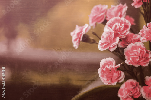 Photo  pink carnations blended with hard wood panel for background, filtered tones