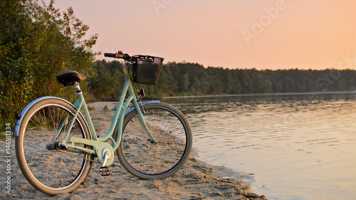 Türaufkleber Fahrrad Vintage bicycle with a basket near the lake during beautiful summer sunset. Copy space.