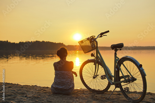 Fotobehang Fiets Beautiful girl with a vintage bicycle sitting on beach sand and enjoying amazing sunset. Back view.
