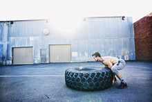 Caucasian Man Working Out With Heavy Tire Outdoors