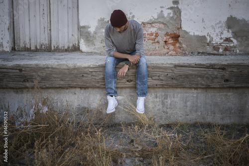 Lonely Hispanic man sitting on urban wall