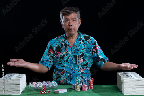 Rich man with stack of banknote and chips in casino плакат