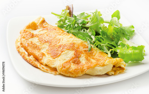 Omelette with fresh salad on white plate