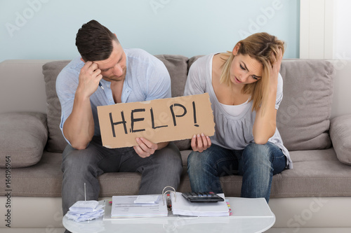 Fotomural  Worried Couple Holding Help Sign While Calculating Bills