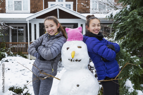 Mixed Race girls posing with snowman wearing pink hat with ears Poster