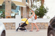Young woman strolling pushchair with baby by the street. Some cars on foreground. Street cafe on background