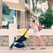 Young woman strolling pushchair with sleeping baby on street