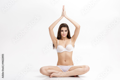 young attractive sporty woman sitting in Lotus position on white background