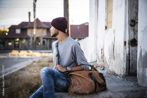 Hispanic man sitting on concrete staircase with bag