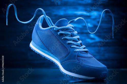 Blue sport sneakers on a wooden background Obraz na płótnie