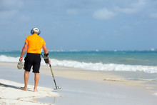 A Man Is Walking On The Beach With Metal Detector To Find Jewellery And Coins. The Man Composed To The Left. Copy Space.