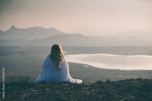 Lonely sad and crying young woman sitting wrapped in blanket on cliff of mountain Poster