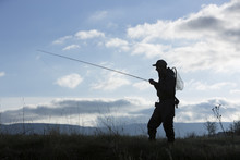 Silhouette Of Man Carrying Fishing Rod In Field