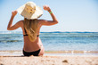 Beautiful young woman in hat sitting happy on sand beach summer vocation