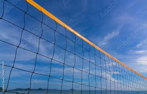 Plakat Zbliżenie plażowej siatkówki sieć na plaży z pogodnym i pogodnym niebem
