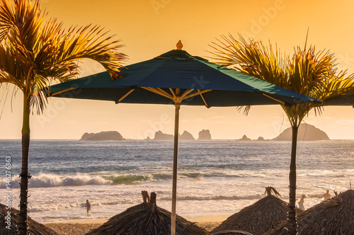 Beach Scene With Palm Trees Umbrellas And Ocean Background