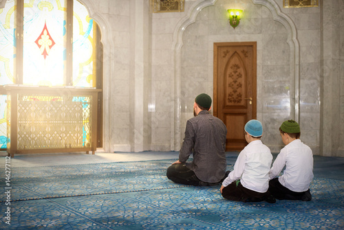 Photo  Father and sons pray in the mosque