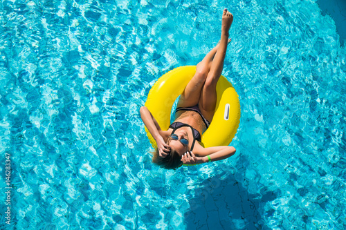 Fotomural Happy young woman in bikini with rubber inflatable float, playing and having a g