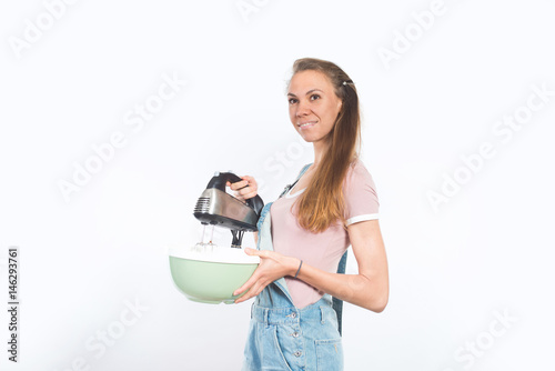 Fotografie, Obraz  Young attractive smiling woman holding bowl and mixer