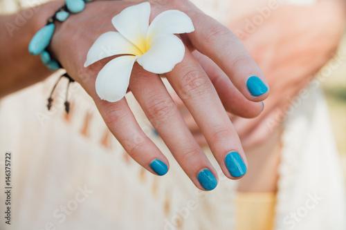 Montage in der Fensternische Plumeria White plumeria Flower on hand With a turquoise bracelet.