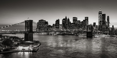 FototapetaBlack & White elevated view of the Brooklyn Bridge and Lower Manhattan skyscrapers at dusk. Skyline of the Financial District with East River. New York City