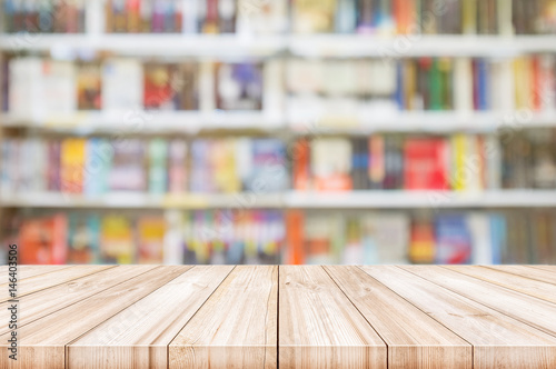 Empty wooden table top with Blur bookshelves in bookstore background Poster Mural XXL