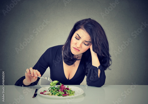 Valokuva  Displeased young woman eating green leaf lettuce tired of diet restrictions