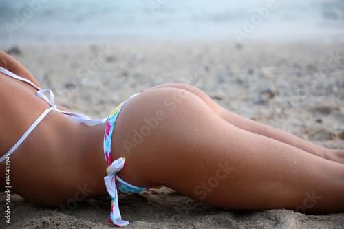 Zdjęcie XXL Sporty młoda piękna kobieta w bikini sunbathing z piaskowatym seksownym kruponem na dennym brzeg. Zdjęcie na zewnątrz styl życia w gorący słoneczny letni dzień. Seksowne pośladki