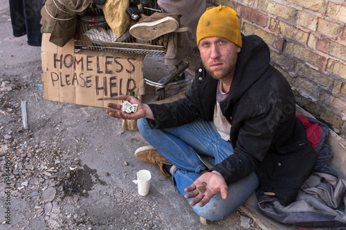 Photo Beggar with cart sitting on the street near the wall and holding dollar in one hand and cents in other, looking at the camera