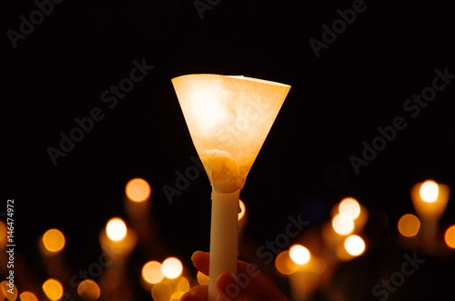 Fotografia  candlelight vigil with shallow depth of field creating round bokeh