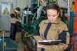 pretty young woman engineer checking for malfunctions at factory