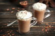 Glass cups of cocoa with whipped cream on wooden table