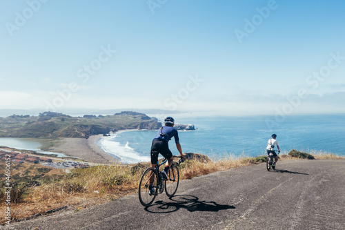 Fotobehang Fietsen Group of cyclists, teammates, friends, descending windy narrow road next to the bay with fog and water and blue skys san francisco in norhtern california.