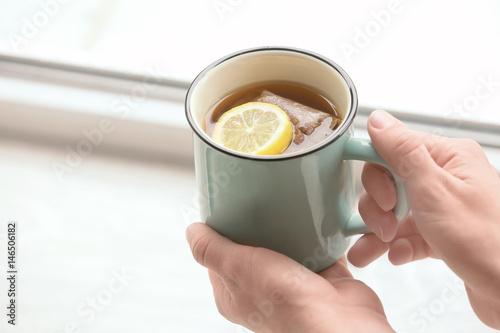 Garden Poster Tea Young woman with cup of hot tea near window, closeup