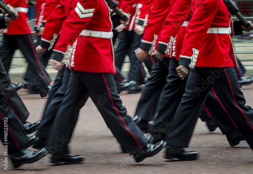 Photo  Queen's Royal Guard soldiers walking in red coat uniforms in motion blur in Lond
