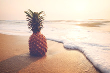 Ripe Pineapples On The Sandy Tropical Beach With Sky In Sunset. Leisure In Summer And Summer Vacation Concept. Vintage Color Tone.
