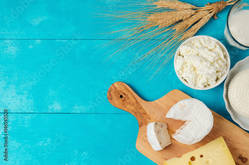 Staande foto Zuivelproducten Milk and cheese, dairy products on wooden blue background. Jewish holiday Shavuot concept. View from above