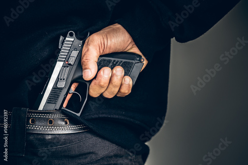 Photo  Robber pulls out a gun tucked in his jean