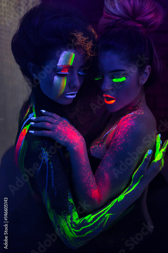 Sexy lesbian fashion models hugging in uv neon light with fluorescent glowing Body Art make-up. Low key dark image. Soft focus image.