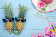 Pineapple with sunglasses ,beach shoes and beautiful hat on wooden background.