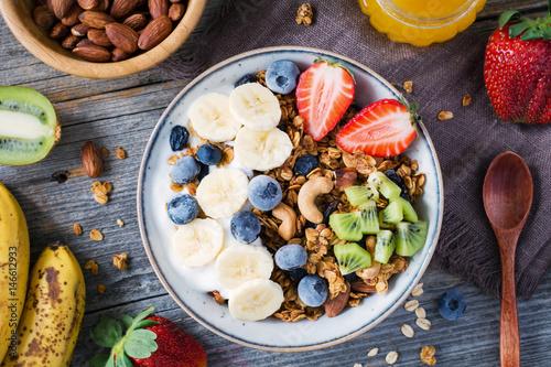 Photo  Homemade granola with nuts and raisins, kiwi, blueberries, banana, strawberries and plain yogurt