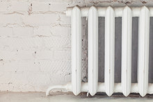 Old White Iron Radiator Central Heating On Brick Wall In Room.