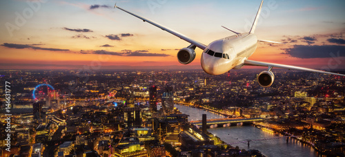 Passengers airplane flying above London city in the sunset light