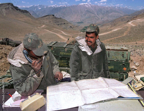 An Indian soldier communicates via a radio phone with other