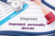 Diagnosis of Dependent Personality Disorder (DPD). On psychiatrist or psychologist table is paper with inscription Dependent Personality Disorder near psychiatric report, hourglass and stethoscope