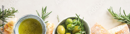 Fototapeta Olivier oil with fresh herbs and bread. Light background. Italian and Greek national food. Top view obraz