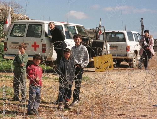LEBANESE CHILDREN OF ARNOUN VILLAGE STAND BEHIND BARBED WIRE