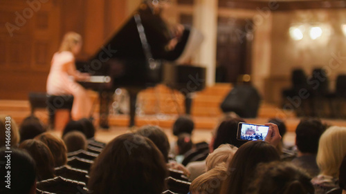Fotografía Spectators in concert hall during performing piano girl- people shooting perform