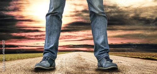 uomo in piedi in mezzo ad una strada al tramonto Wallpaper Mural