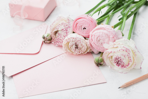 Fotografia Envelope or letter, paper card, gift and pink ranunculus flowers on white table for greeting on Mother or Woman Day
